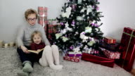 Grandmother is reading a Christmas fairytale for her granddaughter near the Christmas tree. video