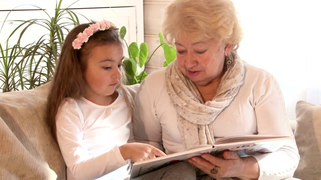 Grandmother reading a book with her granddaughter video