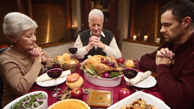 Grandmother saying grace at the Thanksgiving table with her family video