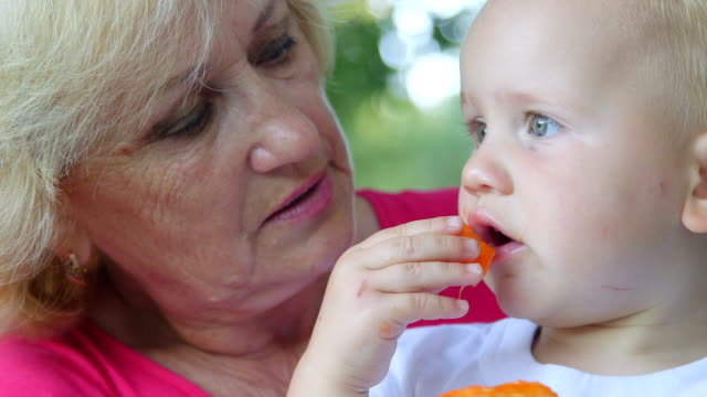 Grandmother with her grandchild eating apricot outdoors video