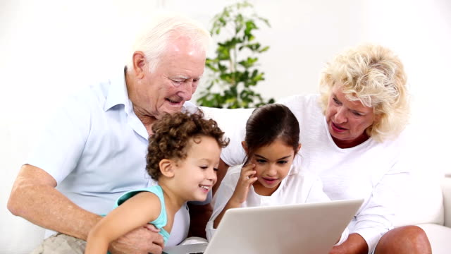 Grandpa and granny using tablet with their grandchildren video