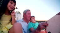 Grandpa reading a story to his grandkids outdoors video