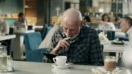 Grandpa working on digital tablet in restaurant video