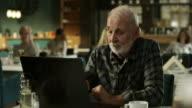 Grandpa working on laptop in restaurant video