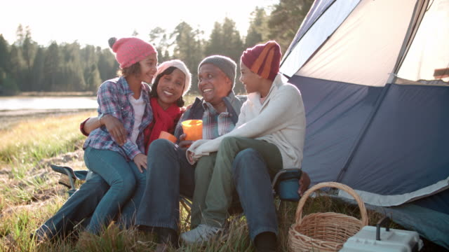 Grandparents and grandchildren relaxing outside tent by lake video