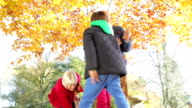 Grandparents And Grandchildren Throwing Leaves In Autumn Garden video