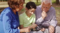 Grandparents And Grandson Studying Homework On Tablet PC video