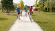 TS Grandparents cycling with grandchildren through the park video