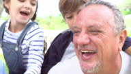 Grandparents Giving Grandchildren Piggyback Ride In Garden video