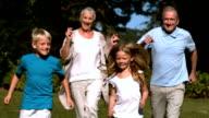 Grandparents running with their grandchildren in a park video