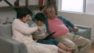 Grandparents sat with their grandson using a digital tablet video