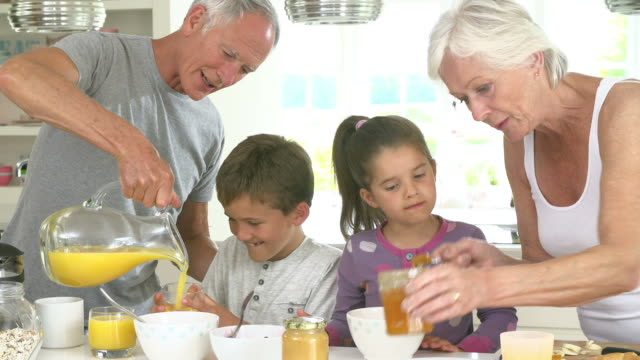 Grandparents With Grandchildren Making Breakfast In Kitchen video
