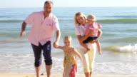 Grandparents With Grandchildren Running Along Beach video