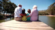 Grandparents with their grandchildren sitting on a lakeside jetty video