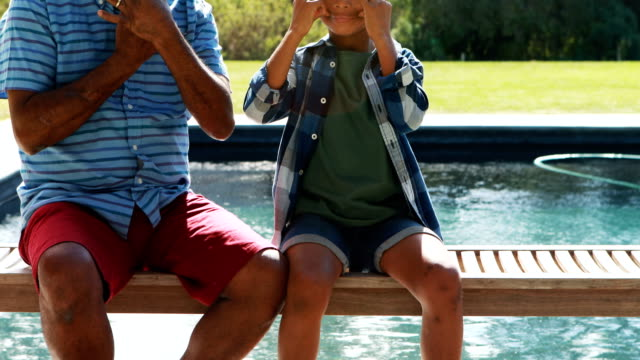 Grandson and grandfather making funny faces near poolside video