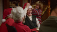 Grandson putting Santa hat on Grandfathers head video