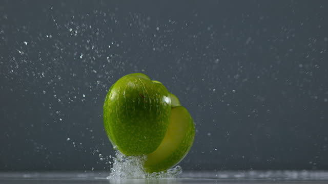 Granny Smith Apple, malus domestica, Fruit falling on Water against Black Background, Slow Motion 4K video