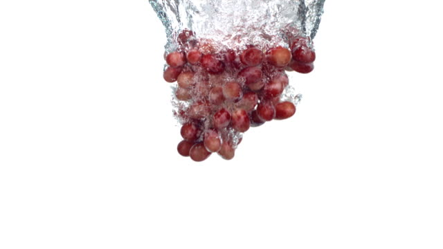 Grapes splashing into water, slow motion video