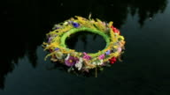 A grass and flower wreath floating on the water. Ethnic decor. Slavic tradition. Ivana Kupala pegan holiday video