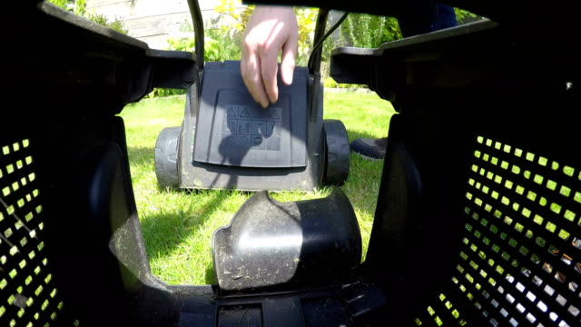 Grass cutting box on a lawnmower in a garden video