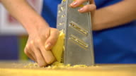 Grating yellow cheese with a metal grater, slo mo video