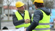 Gratitude between two engineers with safety jackets and yellow hardhats. Outdoors video