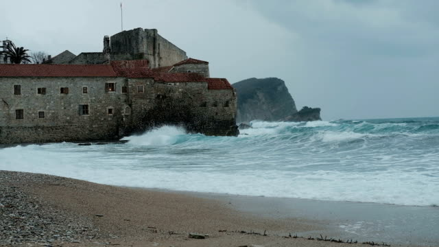 Gray castle washed by sea waters in autumn day video