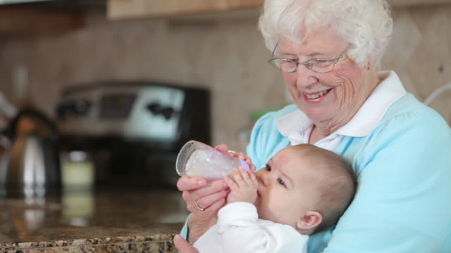 Great Grandmother feeding baby with a bottle video