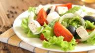 Greek salad on wooden background video