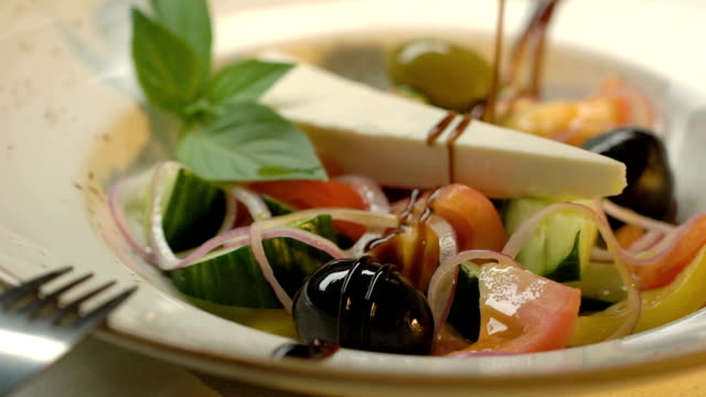 Greek salad with cucumbers, tomatoes, pepper, olives and cheese is decorated with balsamic vinegar. Slow motion. video