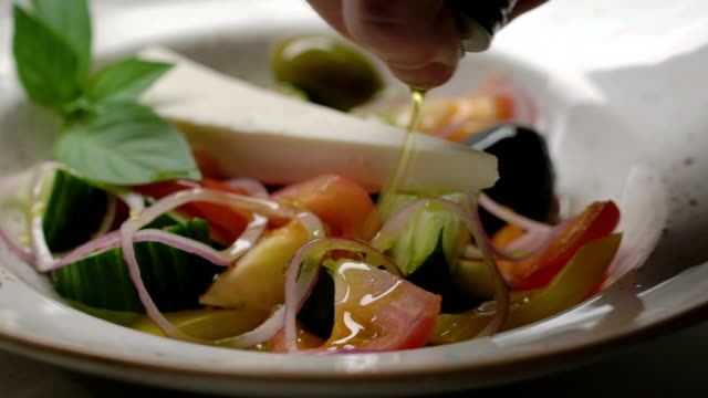 Greek salad with cucumbers, tomatoes, pepper, olives and cheese is dressed with olive oil. Slow motion. video