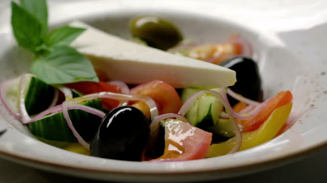 Greek salad with cucumbers, tomatoes, pepper, olives and cheese is decorated with black olive. Slow motion. video