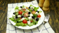 Greek salad with fresh vegetables, feta cheese and black olives rotate video