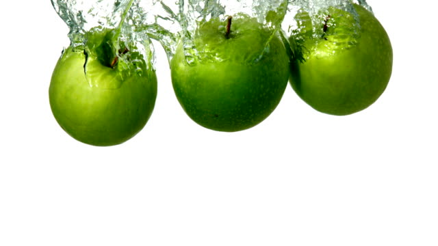 Green apples plunging into water on white background video
