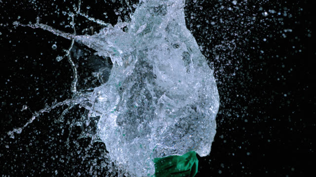 SLO MO of green balloon filled with water exploding video