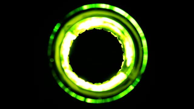 Green beer bottle shimmering on black background video