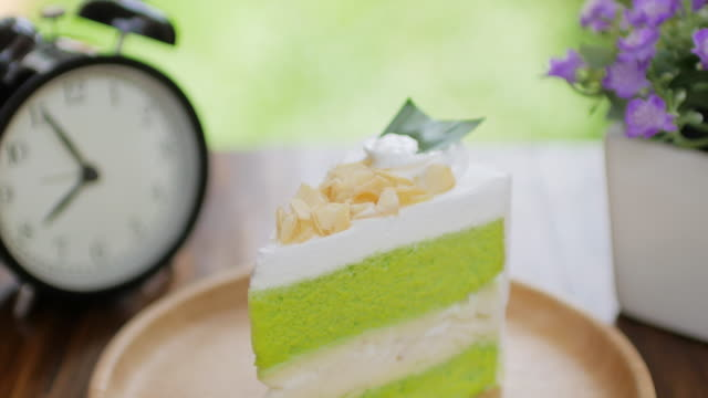 Green Cake Matcha green tea cream cake on wooden table for relax time , dolly shot video