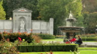 Green city park with fountain, mother with buggy, architecture. Beautiful shot of Europe, culture and landscapes. Traveling sightseeing, tourist views landmarks of Austria. World travel, west European trip cityscape, outdoor shot video