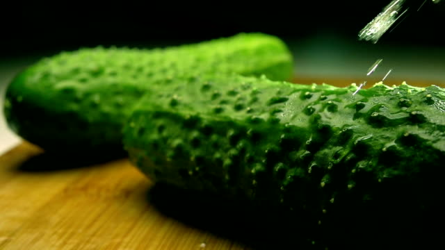 Green cucumbers on wooden cutting board being sprayed with water. Super slow motion shot video