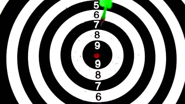 Green dart hitting the bullseye on white background video