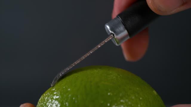 Green Lemon Zest, citrus aurantifolia , against Black background, Slow Motion 4K video