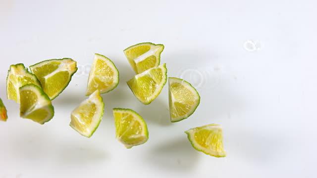 Green Lemons, citrus aurantifolia , Fruits falling on Water against White Background, Slow Motion 4K video