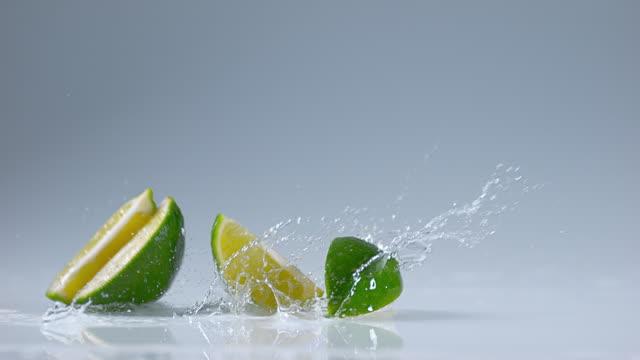 Green Lemons, citrus aurantifolia , Fruits falling on Water, Slow Motion 4K video