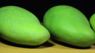 Green Mangoes in panning shot on wooden texture and white black background video
