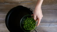 Green peas in glass bowl shift in water video