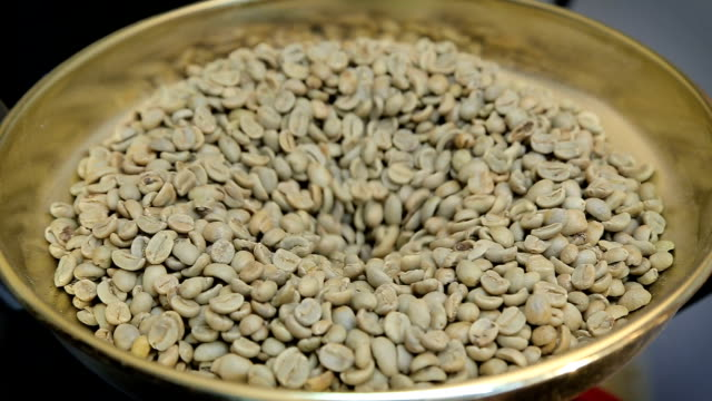 Green raw unroasted coffee beans are poured into a roasting pan video
