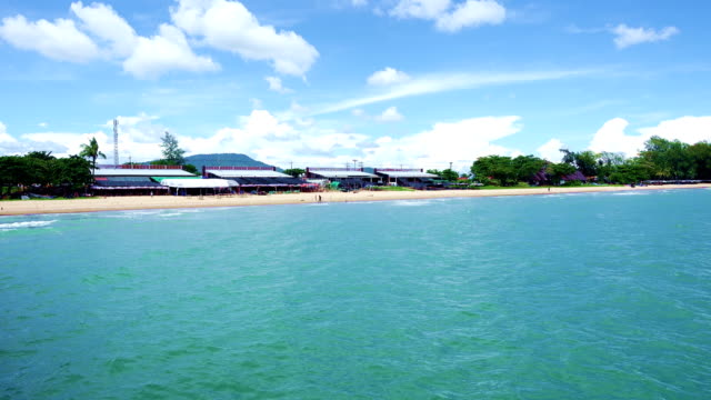 Green Sea Ocean wave to the beach with seafood restaurant along the coast with blue sky video