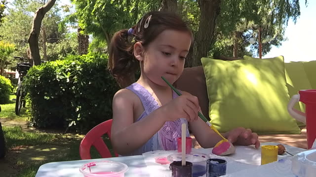 Greenery,Little girl paint rock in house yard video