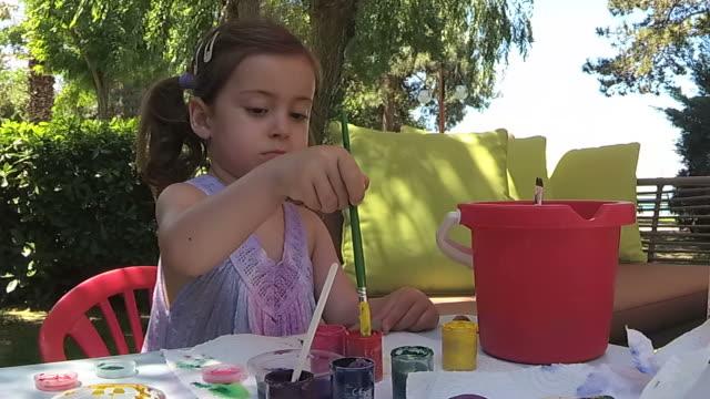 Greenery,Little girl paint rock in house yard video