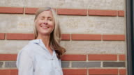 Grey haired mature woman smiling against a textured wall video